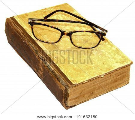 On an old book with a torn binding and a broken spine are glasses isolated on white
