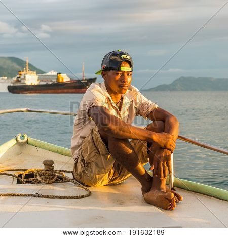 Hell-Ville Madagascar - December 19 2015: Malagasy boatman sailing in the rays of the setting sun on the boat in Andavakotakona Bay near Hell-Ville Nosy Be Island Madagascar.