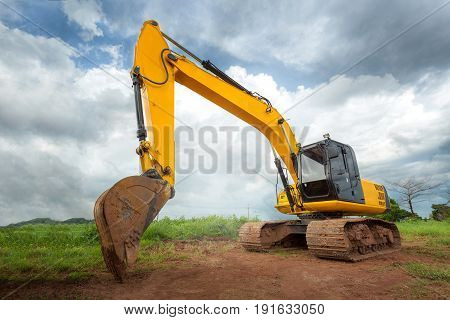 Big excavator on new construction site in the background the blue sky and sun
