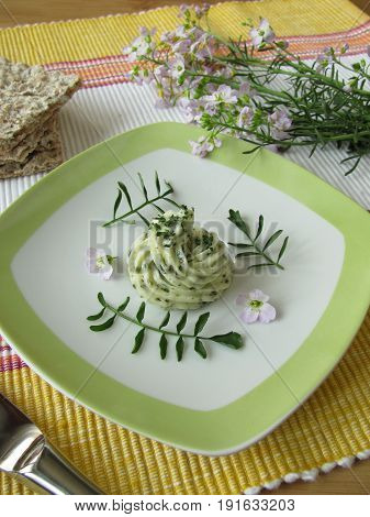 Herbs butter with cuckoo flower on plate