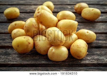raw baby new potatoes on rustic wooden background.
