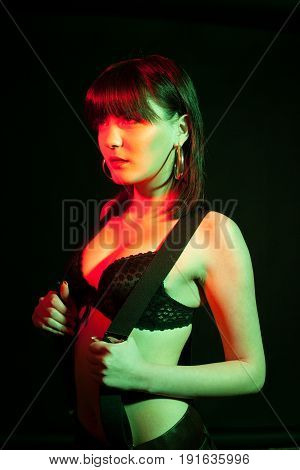 Sensual woman wearing lingerie in red and green light. Studio photo. Hot brunette wearing suspenders