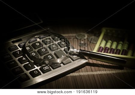 Business Accessories (magnifier, Calculator) And Graphics, Tables, Charts On A Table With Dark Backg