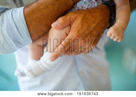 Rough mens hands hold the legs of a newborn baby with a gentle skin