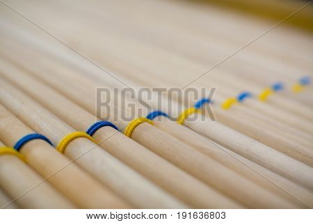 The pattern is a lot of wooden sticks woven with blue and yellow ntkami lie closely related.