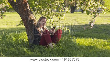 teenage girl sitting under blossomin pink apple tree using smartphone and laughting, wide photo