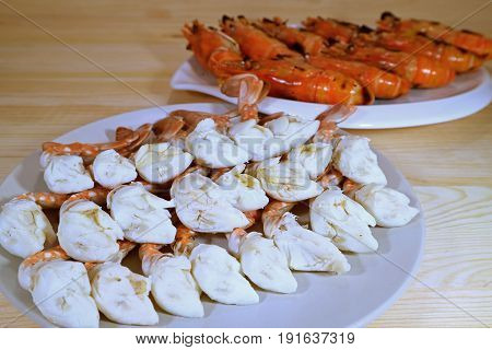Steamed Blue Crab Legs and Grilled Whole River Prawns Served on White Plates