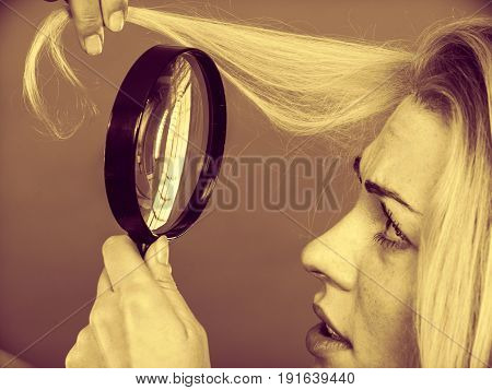 Haircare health problem concept. Unhappy woman looking at ends of her blonde hair through magnifying glass. Sepia