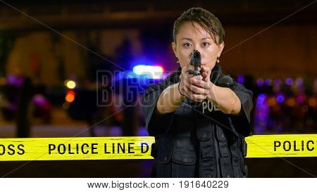 Asian American Policewoman Pointing A Pistol