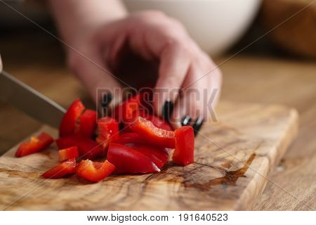 young female hands chopping red bell pepper on kitchen table, shallow focus