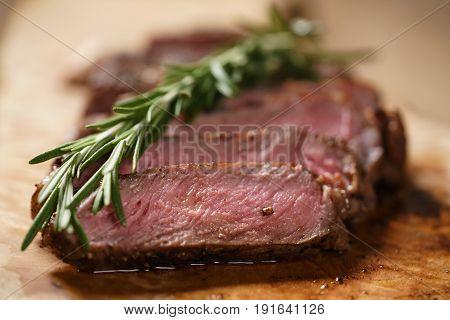 sliced medium rib eye steak with rosemary branch, closeup photo