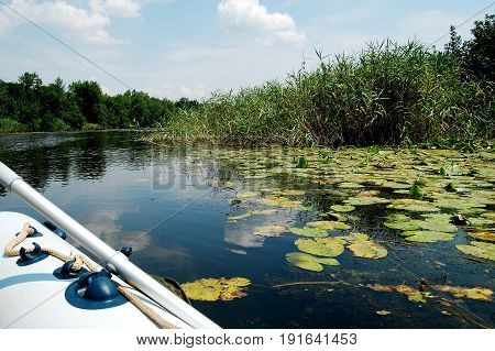 Inflatable boat on a narrow river at noon. Calm water landscape.
