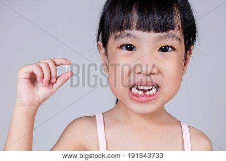Asian Chinese Little Girl Holding Her Missing Tooth