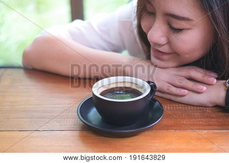 Top view image of Asian woman sit with chin resting on her hands and closing her eyes smelling hot coffee on wooden table with feeling good in cafe
