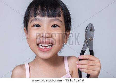 Asian Chinese Little Girl Holding Pliers And Showing The Gap