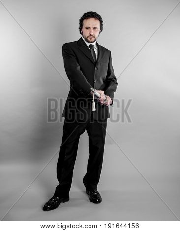 Ninja Businessman in black suit and armed japanese sword on gray background