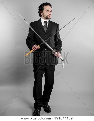 Corporate Businessman in black suit and armed japanese sword on gray background