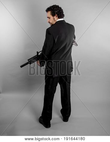Crime Businessman in black suit and armed with machine gun on gray background