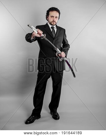 Businessman in black suit and armed japanese sword on gray background