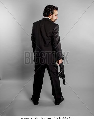 Dangerous Businessman in black suit and armed with machine gun on gray background