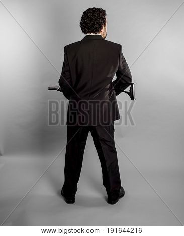 Businessman in black suit and armed with machine gun on gray background