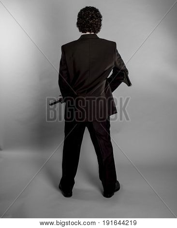 Gangster Businessman in black suit and armed with machine gun on gray background