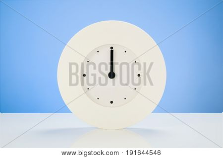 White analog modern clock on white table with blue seamless background