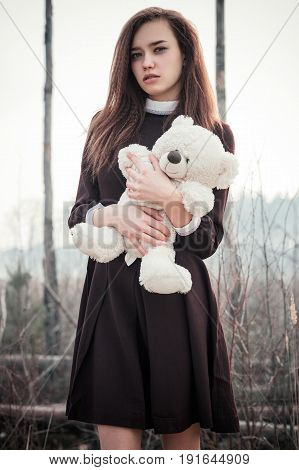 teenager girl with teddy bear toy in hands