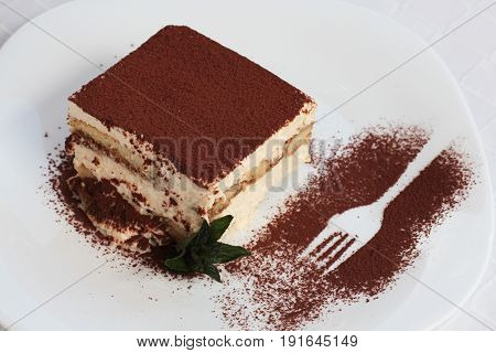 Delicious Tiramisu Cake On Plate On Table On Light Background