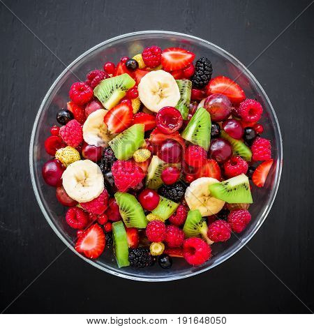 Bowl of healthy fresh fruit salad on dark background. Flat lay. Top view.