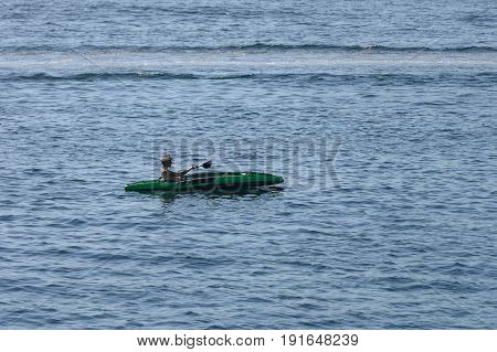 image of young man canoeing in the sea