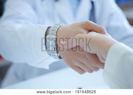 Male doctor shaking hands with patient. Partnership trust and medical ethics concept. Handshake with satisfied client. Thankful handclasp for excellent treatment.