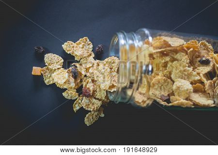 whole grain cereal flakes which mixed berry fruit and raisins. Cereal breakfast on black background. cereal cornflake