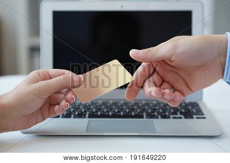 Closeup shot of a woman's hand giving a payment credit card to the seller in computer store. Girl holding a credit card. Shallow depth of field with focus on the credit card.