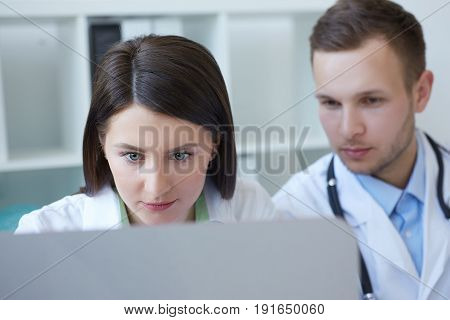 Photo of two doctors together discussing new way of treatment while having a meeting at office. Doctors using desktop computer while discussing new way of treatment.