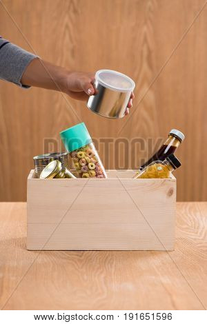 Volunteer With Donation Box With Foodstuffs On Wooden Background