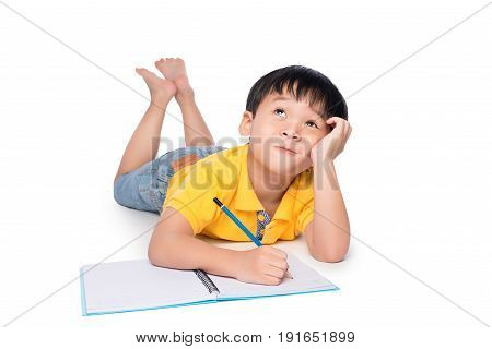 Schoolboy lying on a floor looking up and writing in notebook.