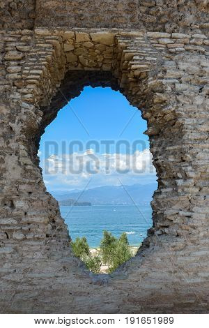 A hole in the wall of the Grotto di Catullo is like a portal with a view of Lake Garda