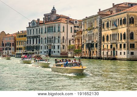 Venice, Italy - May 19, 2017: Water taxis with tourists are sailing along the Grand Canal in Venice. Motor boats are the main transport in Venice.