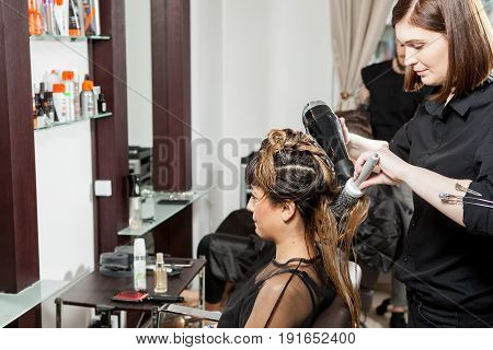 Beautiful woman getting hair treatment at the hair salon. Professional service. New hairstyle. Stylist at work