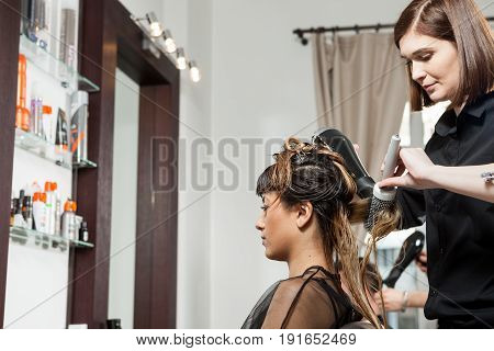 Gorgeous woman getting hair treatment at the hair salon. Professional service. New hairstyle. Stylist at work