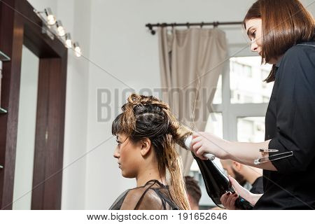 Woman at hairsalon getting luxury treatment. Professional service. New hairstyle. Stylist at work
