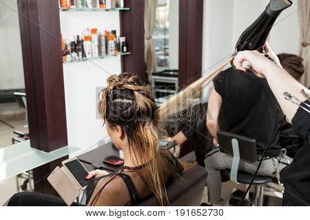 Woman at hairsalon getting treatment. Professional service. New hairstyle. Stylist at work
