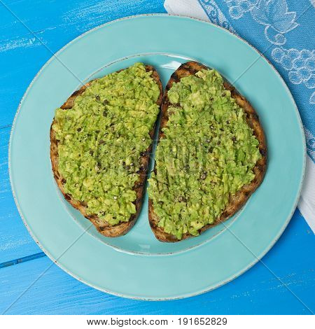Two slices of avocado toast on a blue plate on a painted blue wood background.