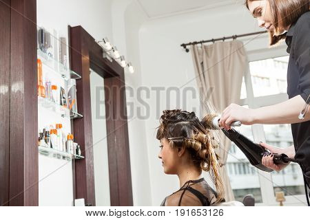 At the hair salon getting a hairstyle. Professional service. New hairstyle. Stylist at work