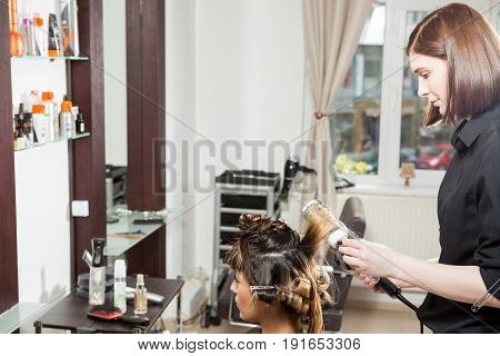 Beautiful woman at the hair salon getting a hairstyle. Professional service. New hairstyle. Stylist at work