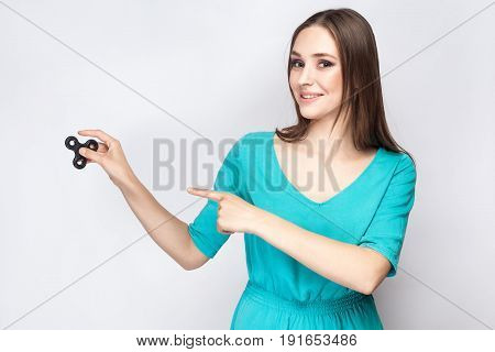 Young beautiful girl holding and playing with fidget spinner. studio shot on white background.