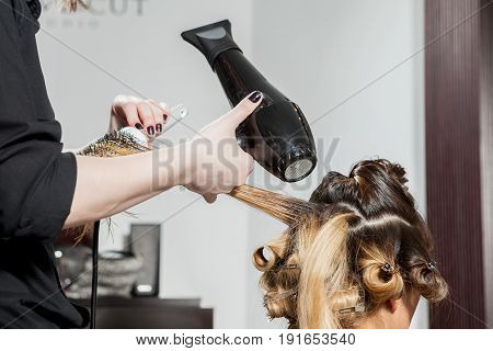Attractive woman at the hair salon getting a hairstyle. Professional service. New hairstyle. Stylist at work