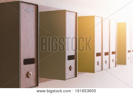 Close focus on vertical mailboxes in modern style with small hole and key hanging on wall by random sorting.