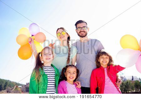 Family of five people with colorful balloons